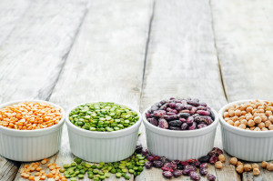 Variety of beans and lentils in small white cups on a wooden table top