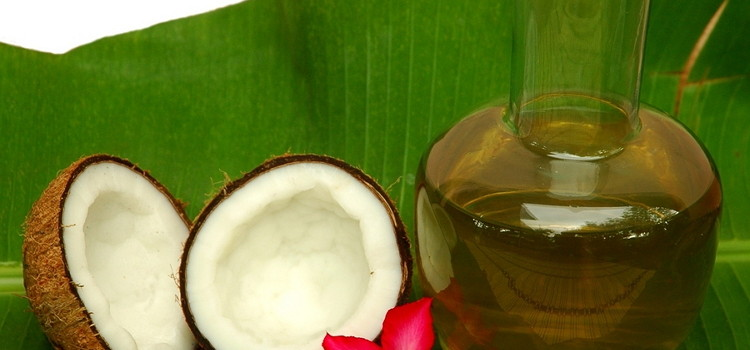 Coconut and coconut oil on a palm leaf with a red flour